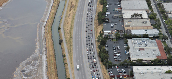 aerial shot of freeway next to body of water congested in one direction
